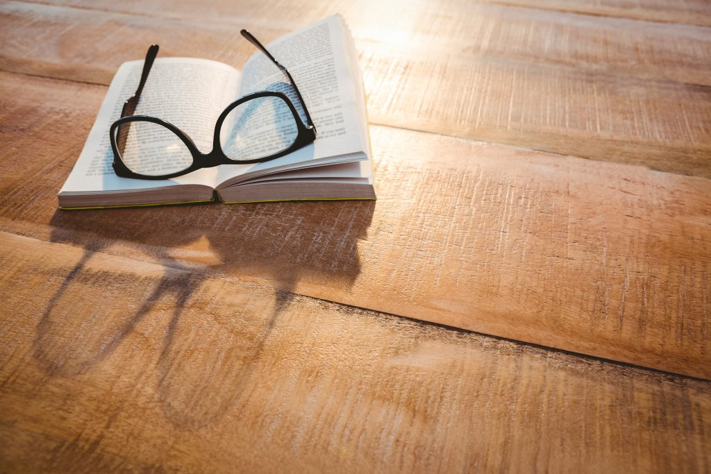 Close up view of a book and glasses on wood desk