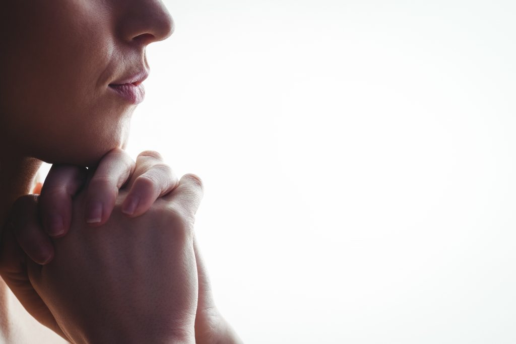 Woman praying with hands together on white background