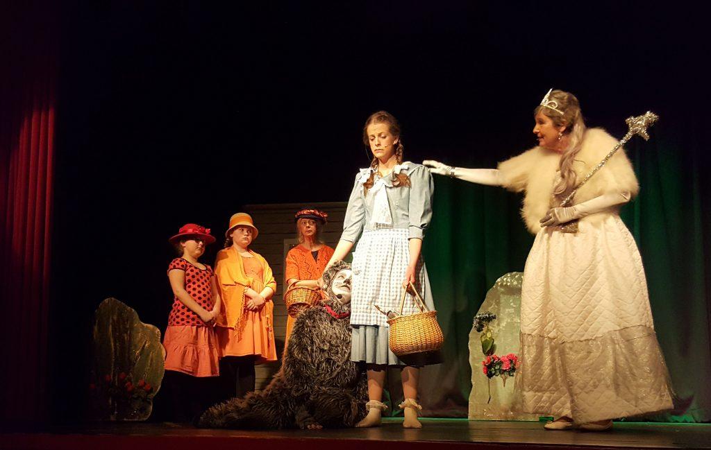 Lena Leijon spelar Dorothy som här syns med hunden Toto som spelas av Annika Hurtig. De möter Häxan Nordan som spelas av Liselott Andersson. I bakgrunden syns Lilleputtarna som spelas av Louise Andersson, Elvira Stenberg samt Ingela Nyman.