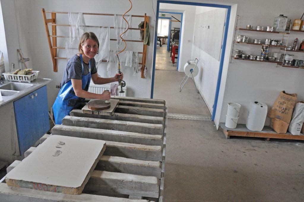 Maria Nordqvist, Varnhem, är elev på Grafikskolan. Med sand och vatten slipar hon ytan på den kalksten som hon ska använda för att trycka sin egen bild, en teckning av den gamla piren i Hjo.