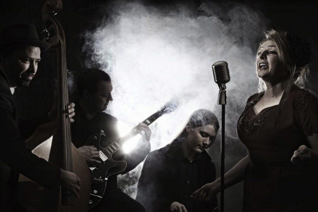 Skövdebandet JazzItch medverkar på Tradjazz-festivalen i Tibro; Lina Warnby sång, Robert Jakobsson gitarr, Fred Warnby trummor och Anders Warnby ståbas.