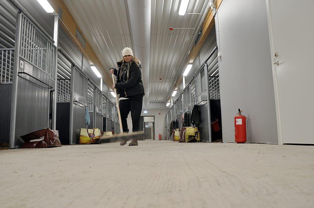 Carina Johansson ser till så att det är rent och fint i det nya stallet. Totalt finns det 24 boxar på den nya anläggningen.