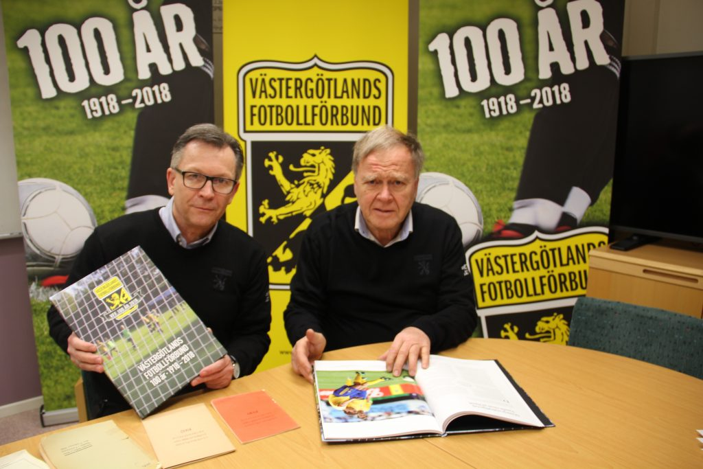 Västergötlands Fotbollförbunds ordförande Peter Karlsson och hedersordföranden Gerhard Sager med den nya boken.