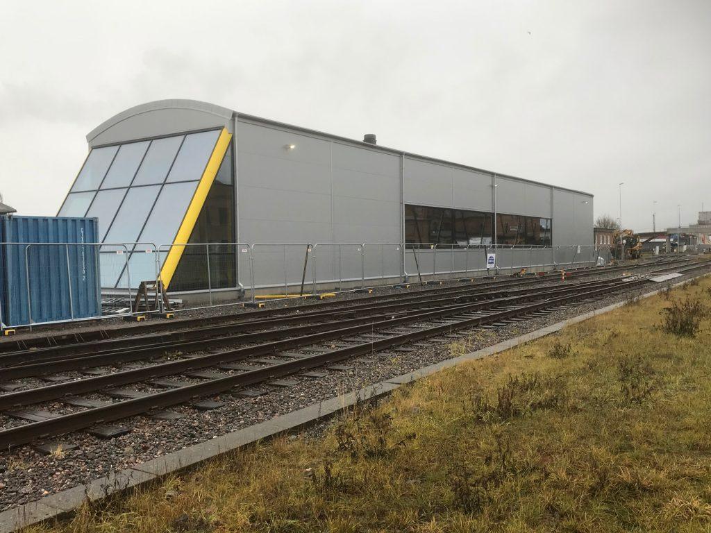 Den nyöppnade depån ligger i anslutning till spåren vid Lidköping station. Designen är gjord för att likna de tåg som finns inuti med snedfönster på ena kortväggen och fönster längs med långsidan. Foto: Västtrafik/Anders Djup
